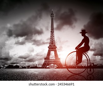 Man on retro bicycle next to Effel Tower, Paris, France. Black and white, vintage mood and red sun light
