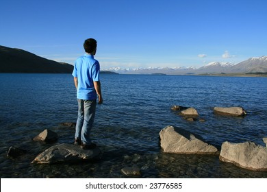 A man on a rock overlooking a rich blue lake
