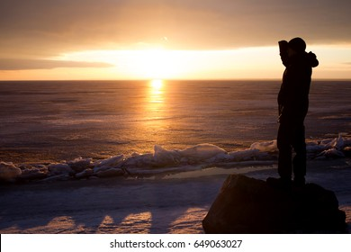 Man on a rock on the sea in the ice - silhouette