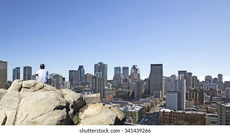Man on a rock watching the city of Montreal