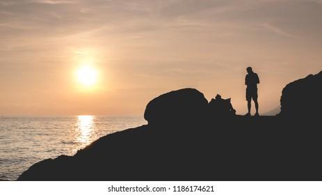 man on the rocks at sunset