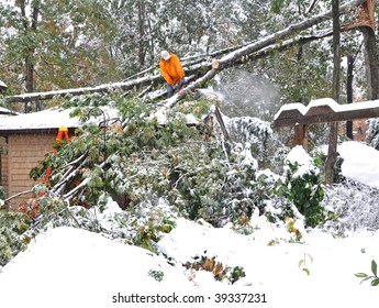 Man on roof cutting fallen tree with chainsaw