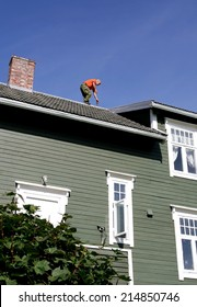 Man on the roof of his house inspecting his chimney