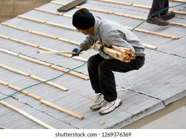Man on roof laying wooden slats preparing to roof a building