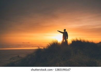 Man on the sand dunes at the sunset