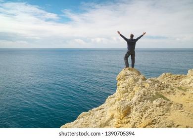 Man on sea cliff edge. Conceptual and emotional scene.