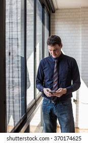 Man on smart phone - young business man in airport. Casual urban professional businessman using smartphone smiling happy inside office building.