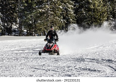 man on snowmobile at winter day