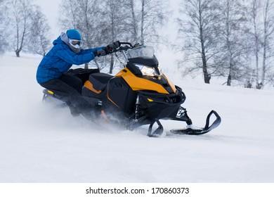 Man on snowmobile in winter mountain