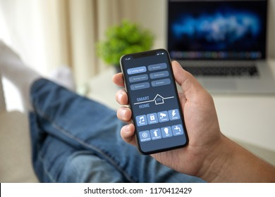 man on sofa holding phone with app smart home on screen in room house