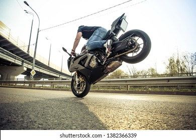 a man on a sport motorcycle is doing the trick stoppi. stunt rider on superbike takes the element of stunt riding. stuntman performs a trick by putting a sportbike on the front wheel. toned