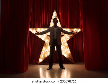 Man on stage with star on background