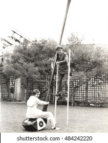 Man on stilts holding onto giant golf club with woman seated on it