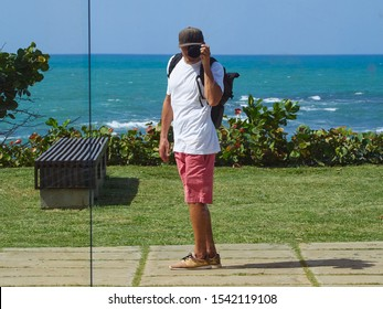 A man on the street photographs himself in the reflection of the building. On the ocean. Sunny day. Dominican Republic.