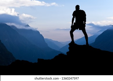 Man on successful hiking, silhouette in mountains. Hiker on top of mountain looking at beautiful Himalayan landscape on sunset, Nepal.