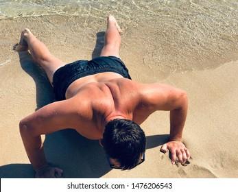 Man on the summer beach, outdoor workout push ups.