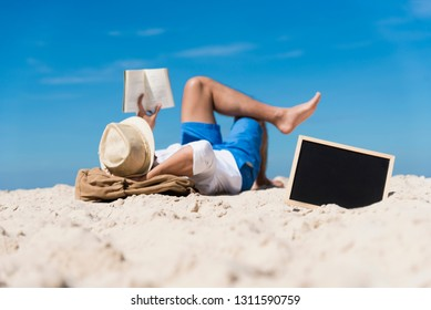 Man on summer island beach relax during holiday vacation. Lifestyle happy tan skin man reading book wear straw hat lay on beach without internet feeling relaxation. Outdoors travel tourist lifestyle