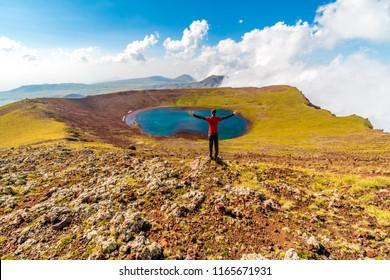 Man on a summit of Azhdahak volcano watching crater lake, Geghama mountains, Armenia