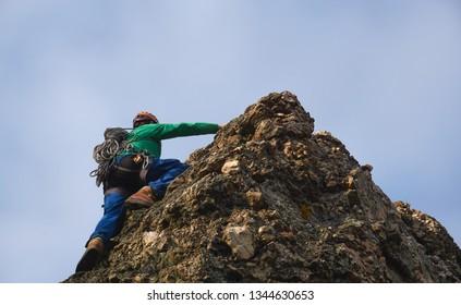 man on the summit of a limestone peak