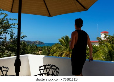 Man on sunny day on rooftop overlooking Sayulita, Mexico