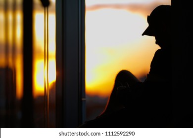 Man on the sunset background. He is located on a high floor and has a beatiful view outside.