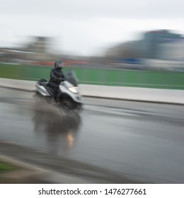 Man on three wheel motorcycle in blurred motion in heavy rain