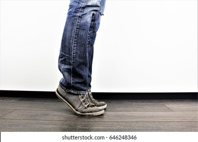 Man on tip toes, anonymous bottom half crop, indoors studio people shot