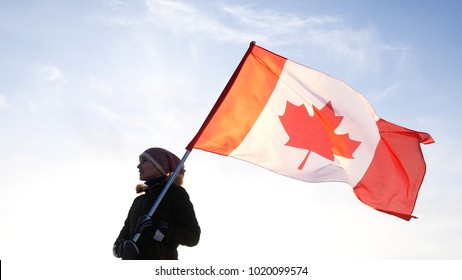Man on the top with Canadian flag. Winner and motivation concept.