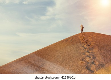 Man on top of a dune in the desert