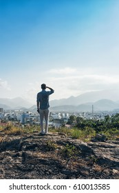 Man on a top of a hill. Fashionable man in white trousers and blue shirt enjoying city and mountains view