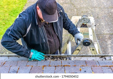 Man on top of ladder cleaning dirt from roof gutter on building  - his hand in messy gloves - view from the top of the roof