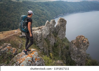 Man on a top of mountain above river canyon