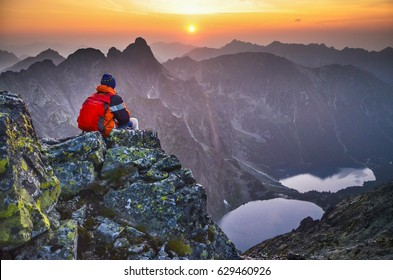 man on the top of mountain with beautiful scenery all around - summer sunset sky, rocks, valley and two lakes