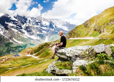 Man on top of mountain. Conceptual design. An elderly man sits on top of a mountain. Active holiday in retirement. Time is one with itself. Mountain landscape in the Alps.