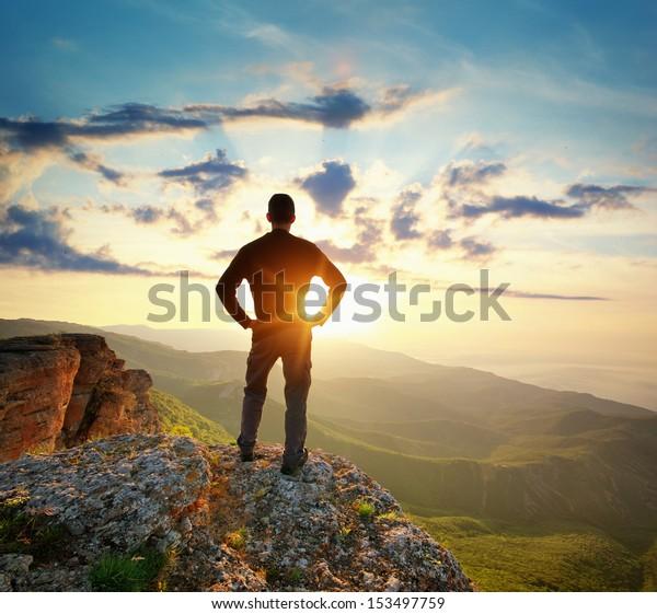 Mann auf der Bergspitze. Konzeptuelle Szene.