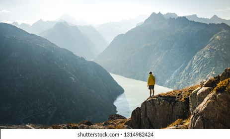 Man on top of mountain. Epic shot of adventure hiking in mountains alone outdoor active lifestyle travel vacations. Conceptual scene.
