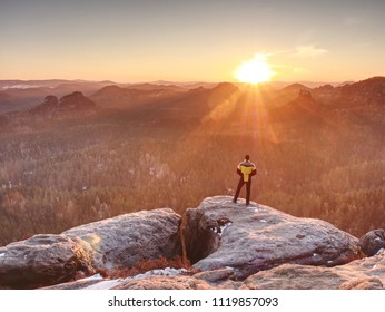 Man on top of mountain. Hiker climbed on peak of rock above foggy valley. Tourist alone looking over landscape at sunset