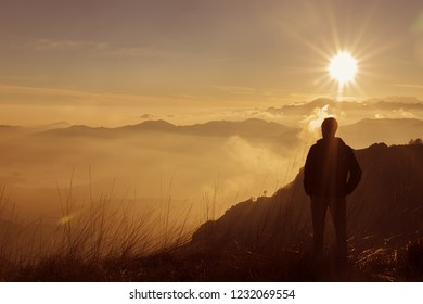 Man on top of mountain. Hiker climbed on peak of rock above foggy valley. Man watch over misty and foggy morning valley to bright morning Sun.