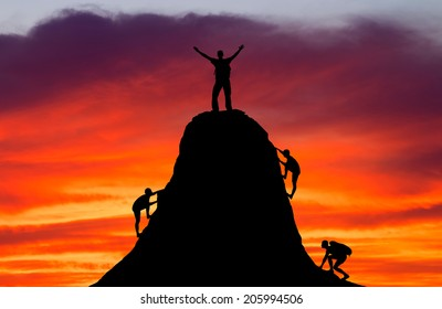 Man on top of the mountain and the other people to climb up on fiery orange background. Rock climber at sunset background. Sport and active life.