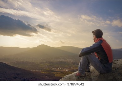 Man on top of mountain sitting on the rock watching a nice sunrise in the village