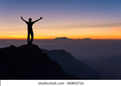 man on top of the mountain spread hand and looking to the sunrise