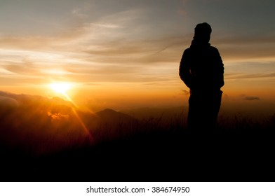 man on top of mountain at sunset, selective focus
