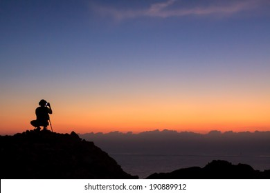 Man on top of the mountain taking photographic at sun rise