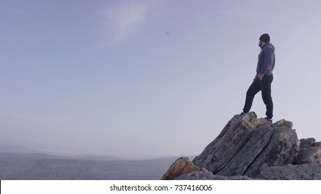Man on top of the mountain. A young, athletic man stands on a high rock