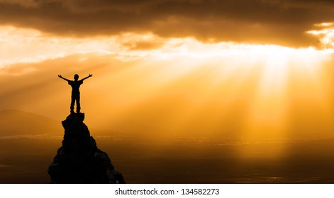 man on the top of a rock  meeting sun  - success concept