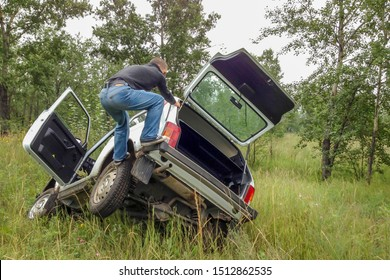 the man on top of the stuck SUV, trying to get the stuck car out of the pit. wheel's stuck. White car on a green forest background, Park. soft focus