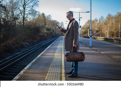 Man is on the train station with travel bag, he looks on the phone, wait for a train. Main UK railway route to Central London