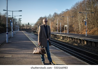 Man is on the train station with travel bag, waits for a train. Main UK railway route to Central London