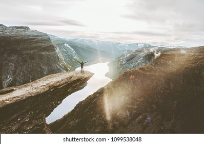 Man on Trolltunga cliff edge happy raised hands traveling in Norway adventure lifestyle extreme vacations outdoor sunset mountains landscape aerial view