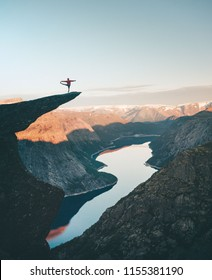 Man on Trolltunga cliff edge happy quince yoga.Traveling in Norway adventure lifestyle extreme vacations outdoor sunrise mountains landscape aerial view
